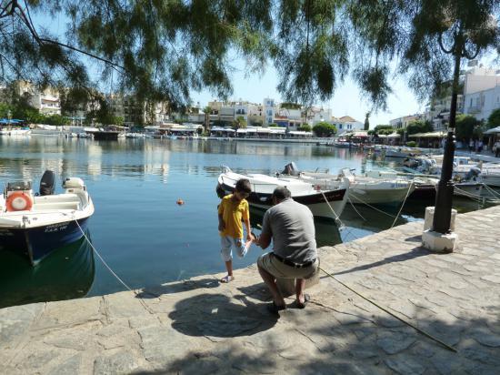папа учит сына ловить рыбу на удочку